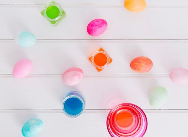 Raccolta di uova di pasqua tra tazze con liquido di tintura