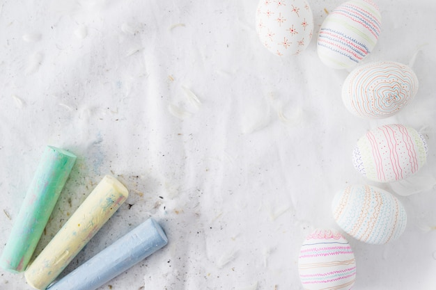 Collection of easter eggs with patterns near quills and chalks on textile
