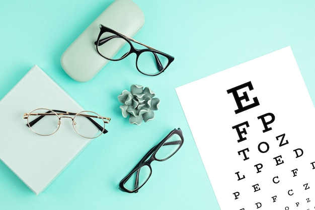 Collection of eyeglasses with eye test table. optical store, glasses selection, eye test, vision examination at optician, fashion accessories concept. top view, flat lay