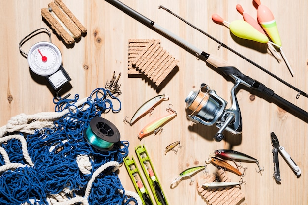 Collection of fishing equipment on wooden surface