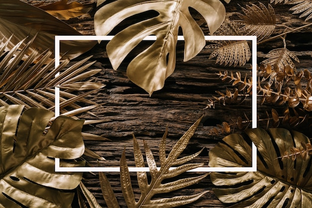 Collection of golden tropical leaves on old wooden background abstract leaf decoration design