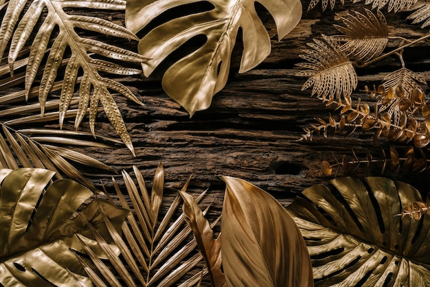 Collection of golden tropical leaves on old wooden backgroundabstract leaf decoration design