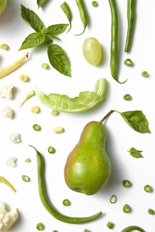 Collection of green vegetables and fruits on white table