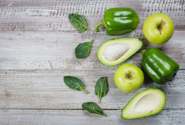 Collection of green vegetables on wooden background, peppers, apple, spinach and avocado.