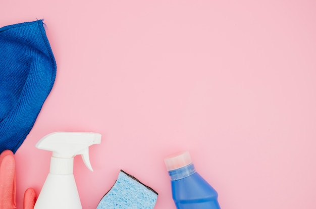 Collection of house cleaning supplies on pink backdrop