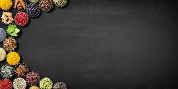黒板にコレクションインドのスパイスとハーブ。黒いテーブル、上面図のカラフルな調味料。レシピやラベル用のスペースのある調味料