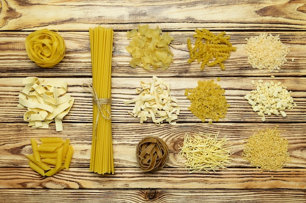 Collection of italian pasta top view on vintage wooden table.