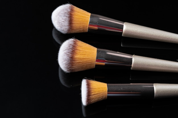 Collection of make up brushes on black background, close up