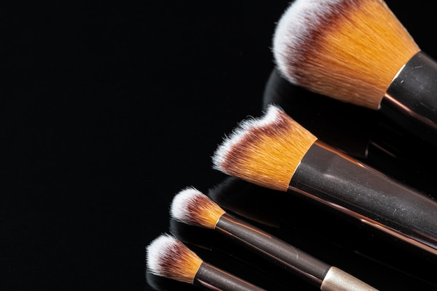 Collection of make up brushes on black background