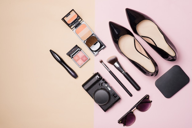 A collection of make up cosmetic beauty with camera and shoes on light color background