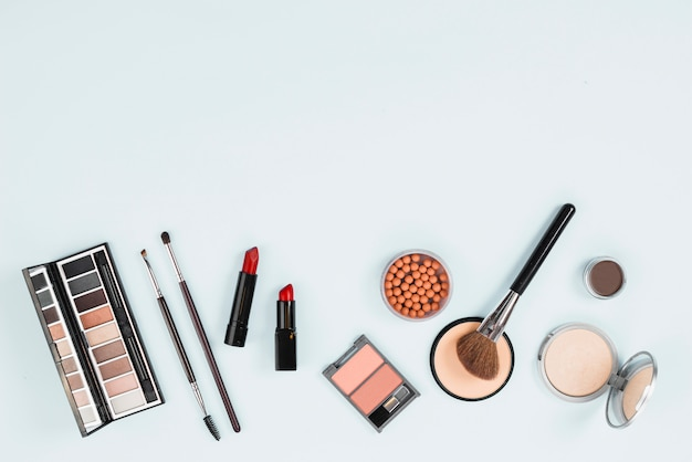 Collection of makeup accessories on light background