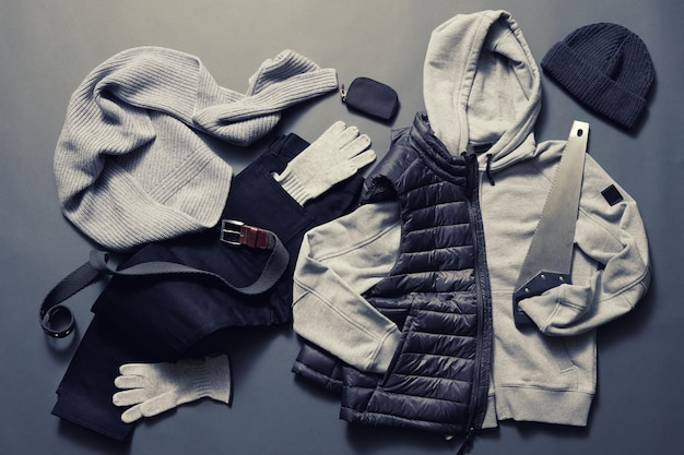 Collection of men's warm clothes on a dark surface