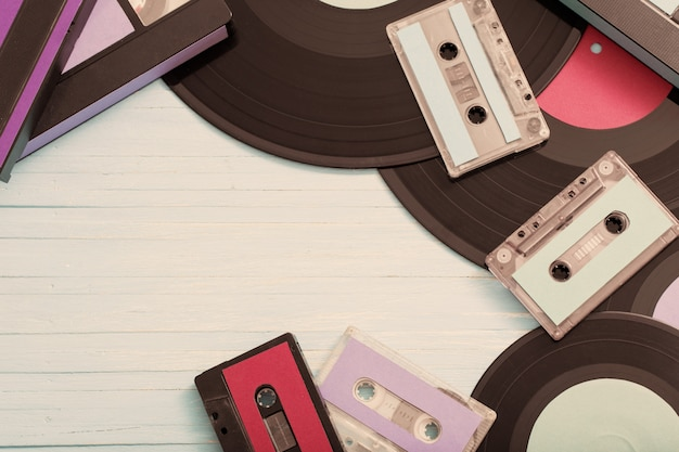 Collection of music tapes, records and video cassettes on wood. retro concept