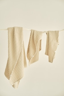 Collection of natural muslin towels of various sizes hang in a row on an unusual wooden hanger