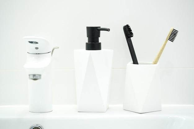 白い背景の上の各種バスルームツール、液体石鹸、歯ブラシのコレクション。ゼロウェイストクリーニング製品のセット。モダンなバスルーム