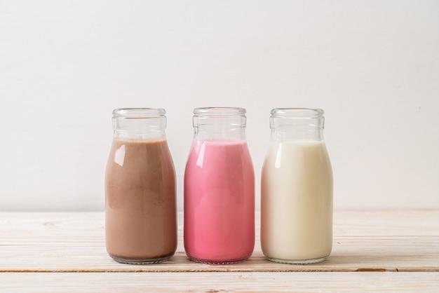 음료 초콜릿 우유, 핑크 우유 및 나무 테이블에 병에 신선한 우유의 컬렉션