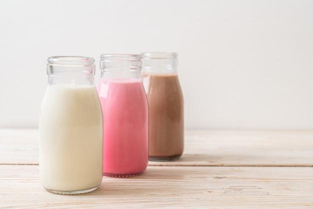 木製のテーブルの上のボトルの飲料チョコレートミルク、ピンクミルク、新鮮なミルクのコレクション