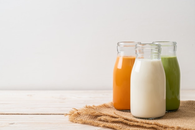 飲料タイミルクティー、抹茶ラテ、木製テーブルのボトルに入った新鮮なミルクのコレクション