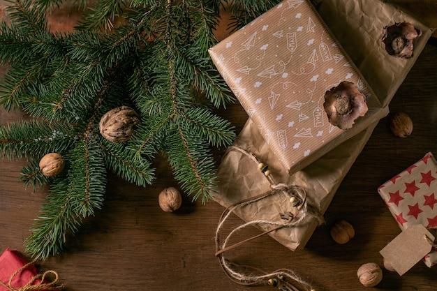 천연 견과류와 계피 스틱으로 장식된 친환경 공예 종이에 크리스마스 선물 상자를 모아 나무 배경 위에 전나무 나뭇가지를 얹습니다. 에코 크리스마스 선물 개념입니다. 플랫 레이