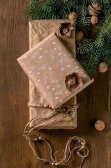 천연 견과류와 계피 스틱으로 장식된 친환경 재활용 공예 종이에 담긴 크리스마스 선물 상자 컬렉션은 전나무 나뭇가지가 있는 나무 배경 위에 있습니다. 에코 크리스마스 선물 개념입니다. 플랫 레이