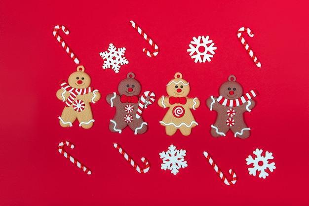 赤い背景の上のクリスマスツリージンジャーブレッドマンのクリスマスおもちゃのコレクション。新年とギフトのコンセプト