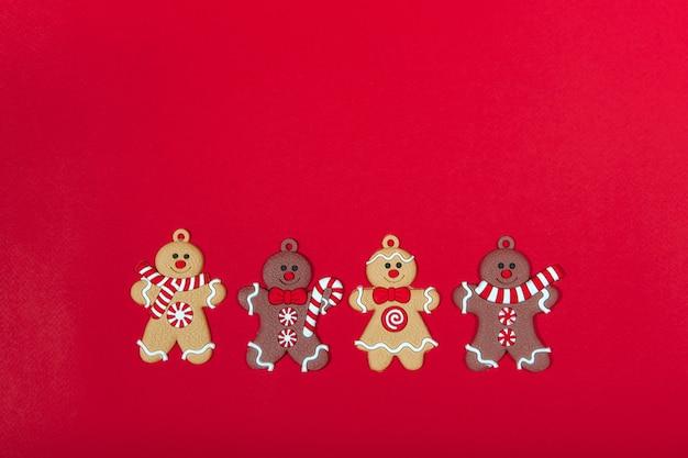赤い背景の上のクリスマスツリーのおもちゃジンジャーブレッドの男性のコレクション。年末年始のコンセプト
