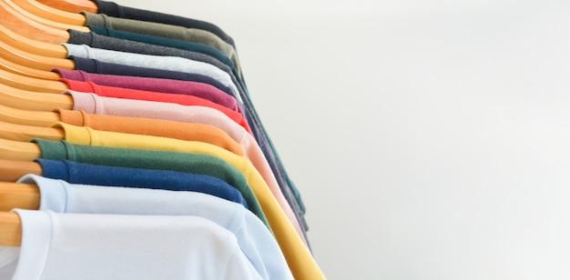 Коллекция цветных футболок, висящих на деревянной вешалке для одежды в шкафу на белом фоне