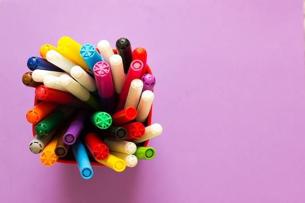 Коллекция цветных фломастеров в чашке на фиолетовом фоне, вид сверху и копировальное пространство.