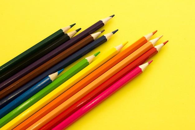黄色の背景の上面図に色鉛筆のコレクション。教育、学校に戻る。概念