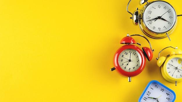 Коллекция красочных будильников в стиле ретро винтаж на ярко-желтом фоне.
