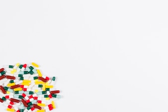 Collection of colorful capsules in the corner of white backdrop