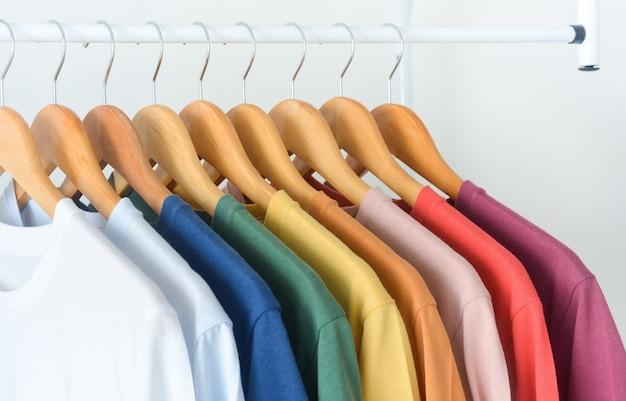 흰색 배경 위에 나무 옷걸이에 걸려 있는 다채로운 티셔츠 컬렉션