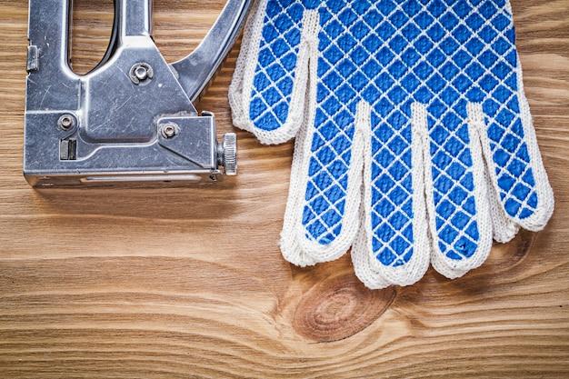 Коллекция строительного степлера и защитных перчаток на деревянной доске
