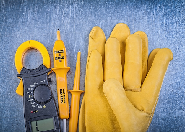 Коллекция защитных перчаток электрического тестера цифровых клещей на металлической поверхности
