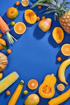 Сбор свежих желтых фруктов и овощей на синем фоне