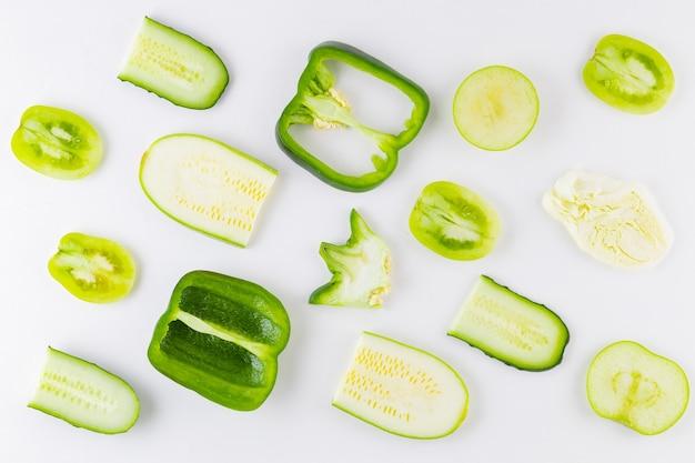 白い壁に緑の野菜や果物のコレクション。上面図。