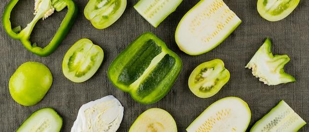 自然な生地の緑の野菜や果物のコレクション。新鮮な緑の野菜のセットです。ビーガン用のピーマン、トマト、キュウリ、キャベツ、ズッキーニ、リンゴ。上面図