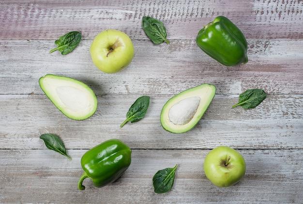 나무 배경, 고추, 사과, 시금치, 아보카도에 녹색 채소의 컬렉션입니다.