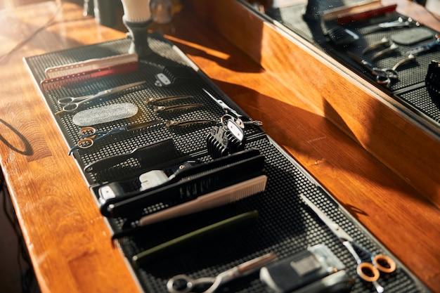 Коллекция парикмахерских инструментов на деревянном столе