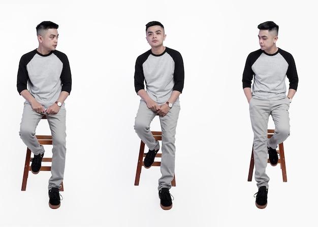 黒灰色のラグランtシャツを着た男のコレクションが椅子に座っていた