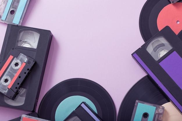 종이 배경에 음악 테이프, 기록 및 비디오 카세트의 컬렉션입니다. 레트로 컨셉