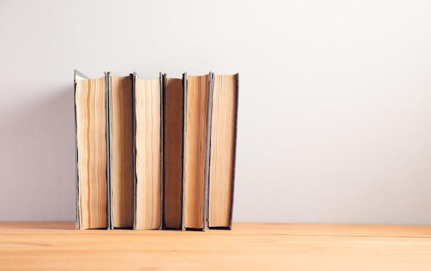 Коллекция старых книг на фоне деревянного стола