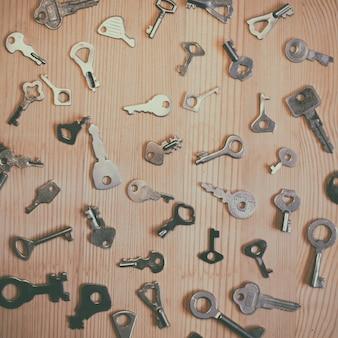 木製の背景に配置された古いキーのコレクション
