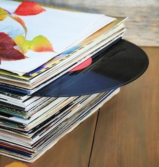 Коллекция старых виниловых пластинок в стопке с осенними листьями.