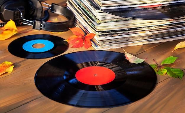 Коллекция старых виниловых пластинок в стопке с наушниками и осенними листьями.