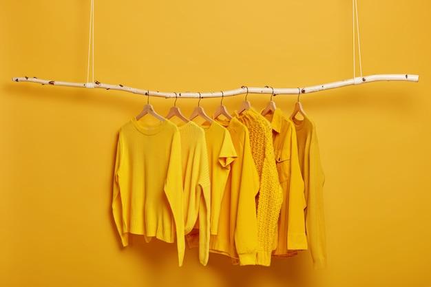 Коллекция однотонных желтых свитеров и курток для женщин висит на вешалке в гримерной. селективный фокус. модная зимняя или осенняя одежда.
