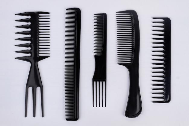 白で隔離される髪のためのプラスチック製の櫛のコレクション。プロの美容ツール。