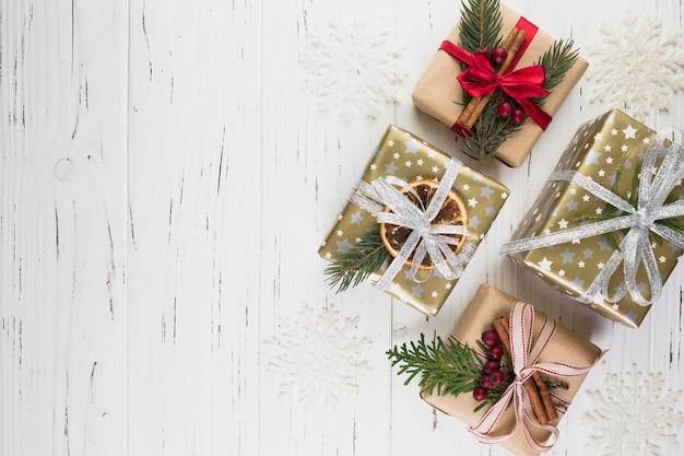 Коллекция настоящих коробок в рождественском обложке между орнаментальными снежинками
