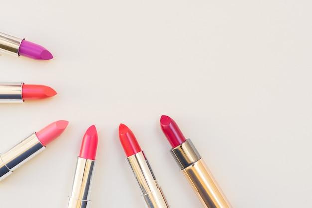 瞳孔のコレクション、ピンクと赤の光沢のある口紅、コピースペース付きのフラットレイトップビュー