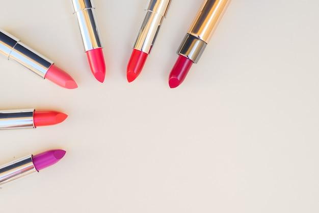 瞳孔のコレクション、ピンクと赤の光沢のある口紅、コピースペース付きの上面図